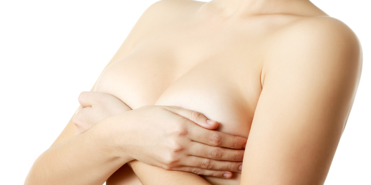 woman examining breast mastopathy or cancer over white